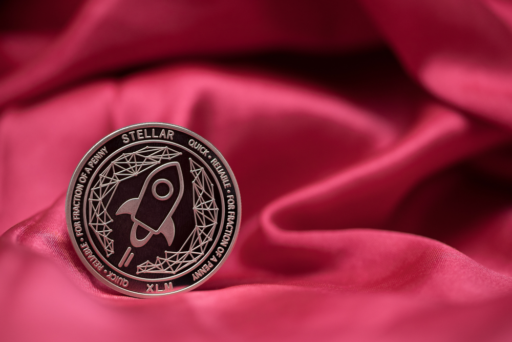 Stellar XLM cryptocurrency physical coin placed on red silk like material - Image